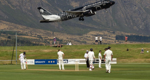 An Air New Zealand jet takes off above the cricketers during day one of the four  day warm up International cricket match between New Zealand and England played at the Queenstown Event Center in Queenstown on February 27, 2013.  TOPSHOTS      AFP PHOTO / Marty MELVILLE